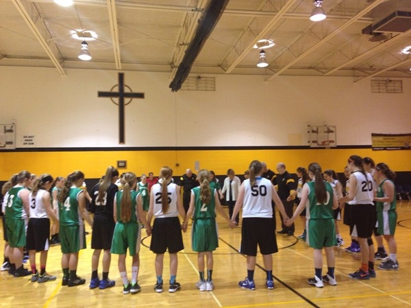 Opposing teams praying after their basketball games at Our Lady of Lourdes Catholic School