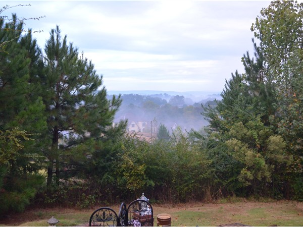 A view from the back yard looking out over the mountains on a foggy day