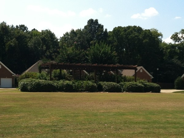 A beautiful landscaped park area with trellis located in Highgrove