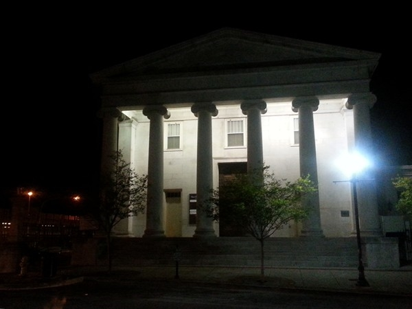 The Old First National Bank building on the westside of the Square on a springtime evening.