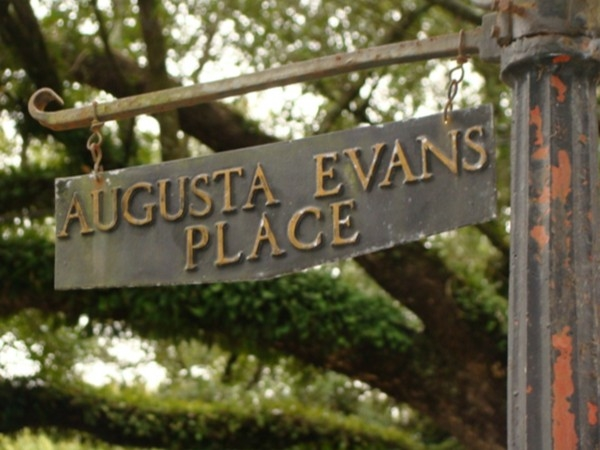 The aging sign hides Augusta Evans Place among huge oak trees.