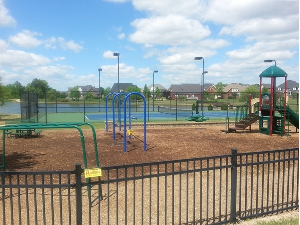 The playground with the lighted tennis court in the background at Heritage Provence