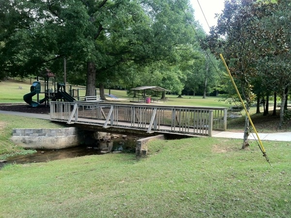 Pleasant Grove Park with water stream under bridge.