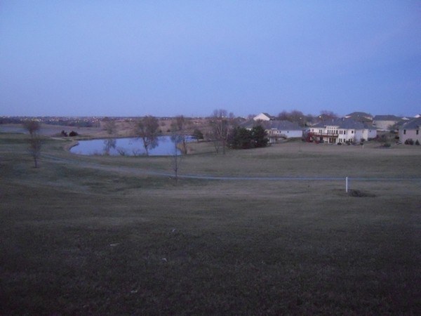 View of one of the fairways with a pond surrounded by homes