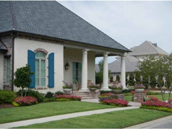 A home with a beautiful front porch and lush landscaping in Grand Pointe