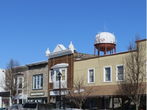 Historic row of buildings in East Rochester with water tower behind