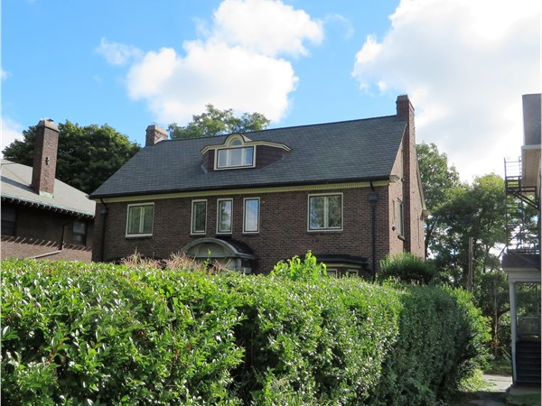 Large brick home hidden by a solid ten foot hedge on Lake Avenue in Rochester
