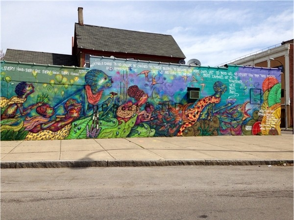 A colorful wall mural adorns the corner of Frost Ave. and Genesee St.