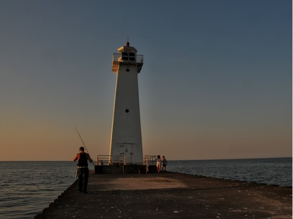 Fishermen gather at the Sodus Point Lighthouse at sunset.