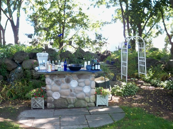 Stone outdoor bar and glass garden behind at the Senator's Mansion