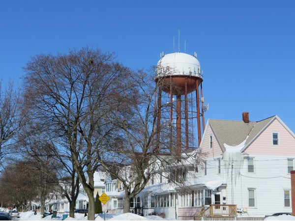 Winter view of a residential street in East Rochester with the water tower in the background
