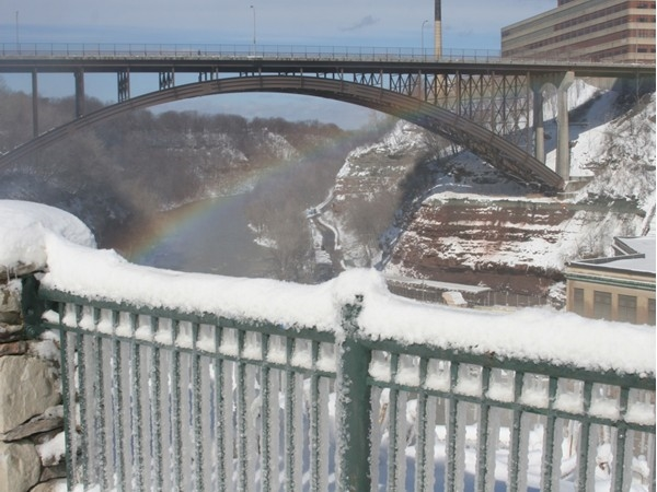 The Pedestrian Bridge in the winter with a rainbow from the mist of the High Falls