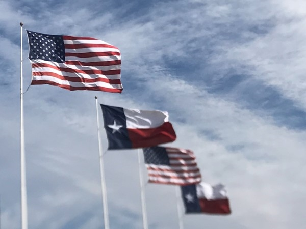If you drive I-30 east of downtown you may recognize these flags flying high today
